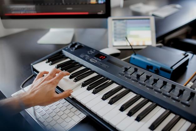 作曲家がレコーディングスタジオでピアノの鍵盤を手に
