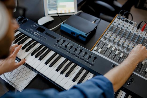 レコーディングスタジオでピアノの鍵盤を演奏する作曲家