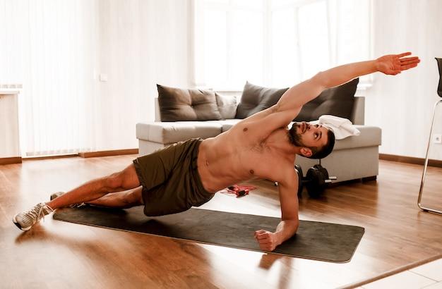 上半身裸の男が自宅でワークアウト