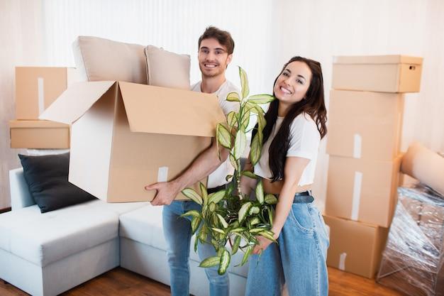 引っ越しの日に新しい家で段ボール箱と幸せなカップル。