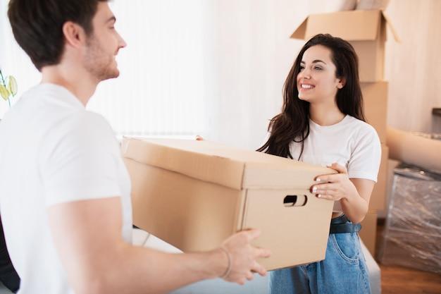 新しい家で大きな段ボール箱を運ぶ若いカップル。