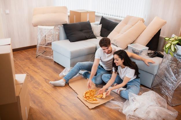 引っ越しの日にピザを食べて幸せな家族。新しい家に一緒に座って休憩時間を楽しんでいる若いカップルの写真。