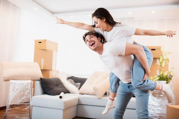 幸せな夫と妻は、一緒に自分のアパートに引っ越すことを楽しんでいます。引っ越しの日に段ボール箱の近くのリビングルームで大喜びの若いカップルのダンスを楽しませる、
