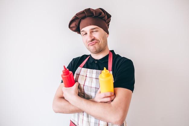 Молодой человек изолированный над белой предпосылкой. положительный уверенно профессиональный повар позирует на камеру с кетчупом и горчицей в руках.