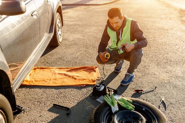道路脇の車の修理に疲れた労働者または運転手