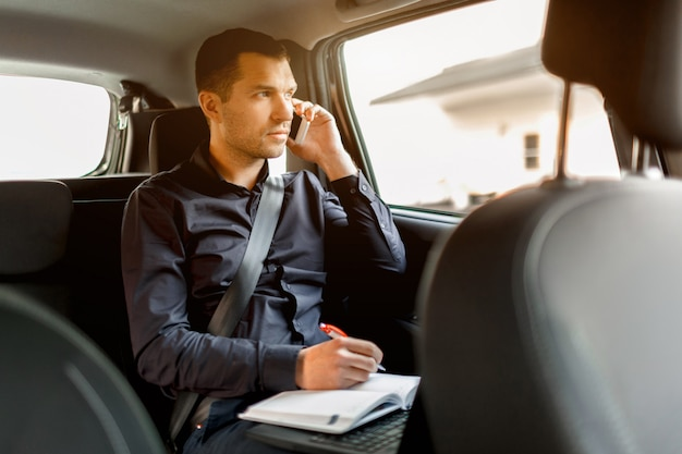 タクシーで忙しいビジネスマン。マルチタスクの概念。乗客は後部座席に乗り、同時に働く。スマートフォンで話し、ノートに書き込みます。