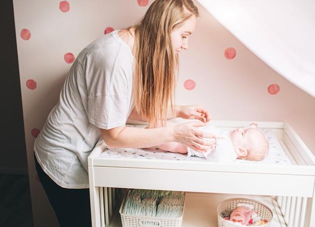 Мать и новорожденный ребенок в детской. мама делает упражнения для ребенка. дисплазия и мышечный тонус