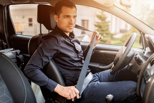 安全運転のコンセプト。男性がシートベルトを締めています。運転前