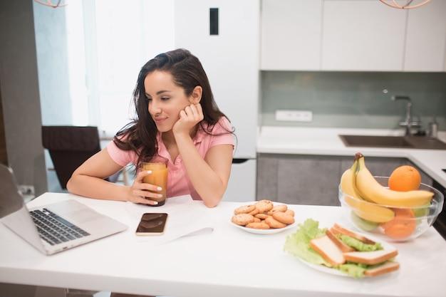 Красивая черноволосая женщина работает из дома. работник сидит на кухне.