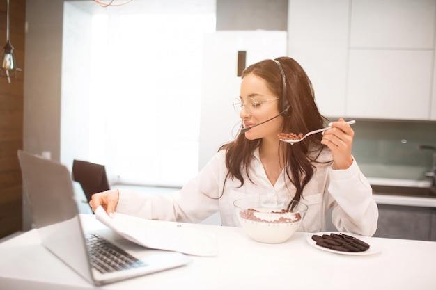 Женщина работает из дома. сотрудник сидит на кухне и много работает на ноутбуке.