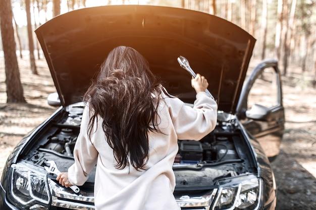 車が故障した。道路での事故。女性がボンネットを開けて、エンジンと車のその他の詳細をチェック