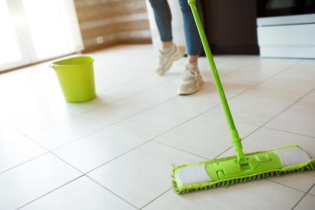 キッチンで若い女性。緑のモップで床を掃除します。ローカットビュー。床をよりきれいにします。後ろに水が付いている緑のバケツ。