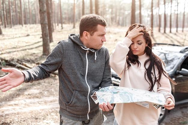 森で迷子になった男女。彼らは地図を持って立っており、次にどこへ行くかわからない。