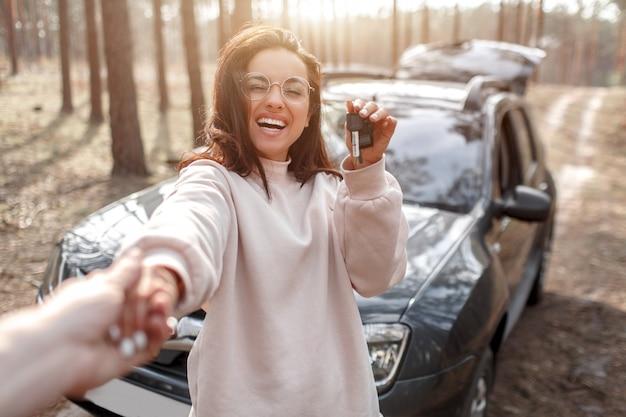 車での旅行。美しい黒髪の女性の車。国の休暇。彼女は車のキーを手に持っています。