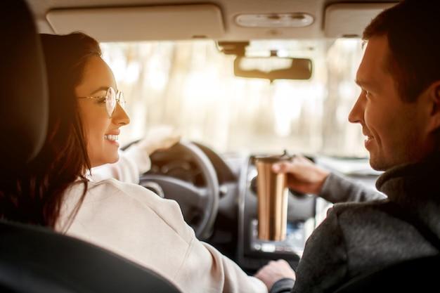 幸せな若い家族が森の中の車に乗る。女性が車を運転し、男性が近くに座っています。車のコンセプトで旅行