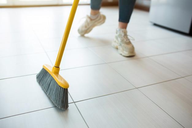 キッチンで若い女性。スニーカーの女の子のローカットビューは、一人で床を掃除します。家の台所を保持しています。明け。