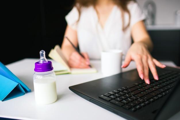 キッチンで若い女性。リモートで自宅で働く白いブラウスの少女のビューをカットします。ノートに書き込んでキーボードで入力します。牛乳と哺乳瓶が前に立っています。