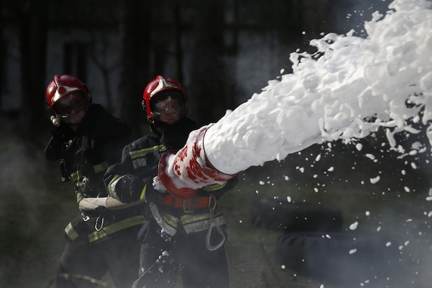 Тушение пожара. пожарные работают. заполните пену огнем. решительные пожарные. борьба с огнем.