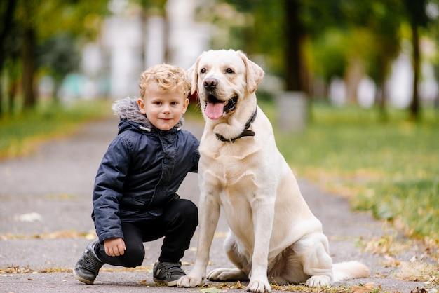 外の公園で犬と一緒に座っているかわいい愛らしい白人男の子の肖像画。動物の家庭用ペットを抱いた子供の笑顔。幸せな子供時代のコンセプト