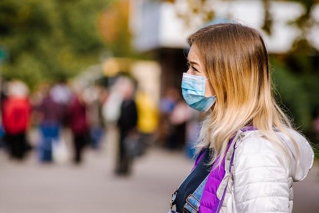 Девушка стоит у дороги в защитной медицинской маске. густой смог на улицах города.