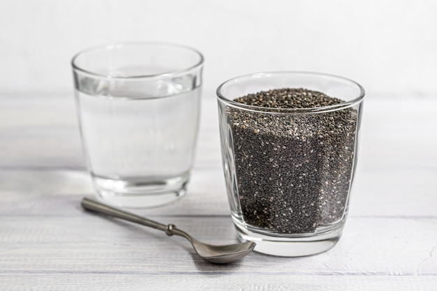 Семена черного чиа в стеклянной посуде и воде, в которой они пропитаны. с металлической ложкой.