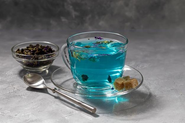 Чашка горячего голубого чая с цветами гороха. голубой горошек. для здорового питья, детоксикации организма. серый стол.