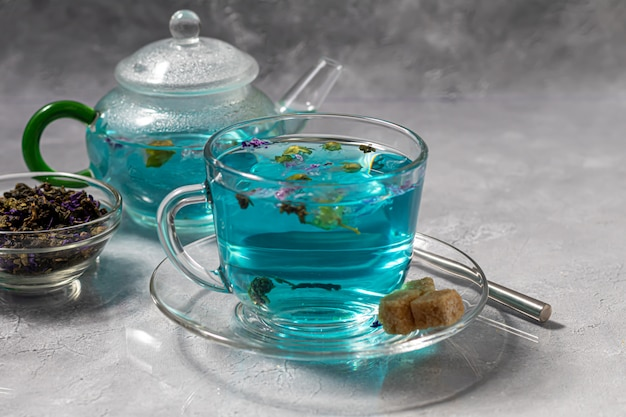 エンドウ豆の花が入った熱いブルーティーのカップ。ブルーピース。健康的な飲酒のために、体を解毒します。灰色のテーブル。