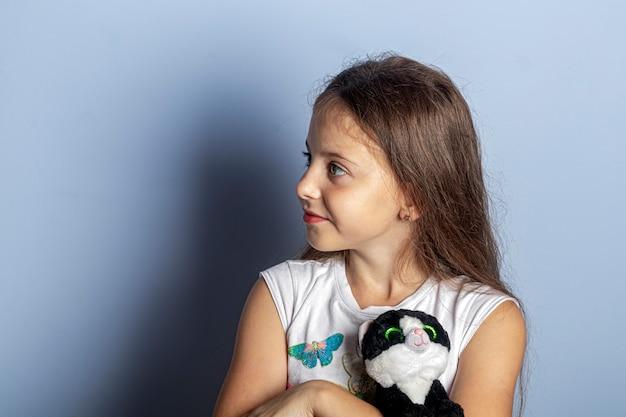 ライトの上に彼女の手で彼女のお気に入りのアイテムを持つ美しい長い髪の少女