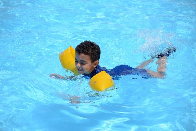 若い水泳、青いプールの水で泳いでいる少年