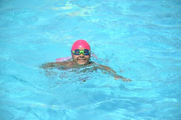 若いスイマー、青いプールの水で泳いでいる少女