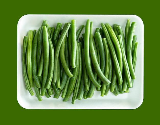 新鮮な緑のひも豆のヒープの白い皿