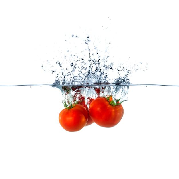 Свежие красные помидоры, тонущие в воде