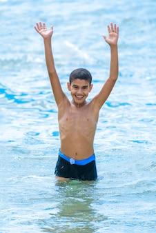Активный счастливый мальчик, играя в синей морской воде с поднятыми руками