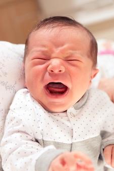 Милый новорожденный ребенок громко плачет с помощью жестов на лице
