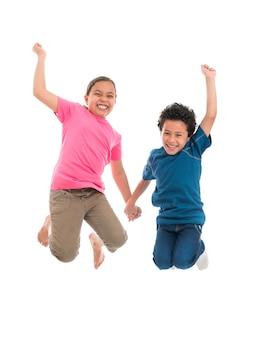 白い背景で隔離の喜びでジャンプアクティブなうれしそうな子供