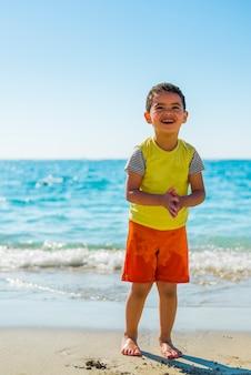 日光の下でビーチで遊び心のある少年