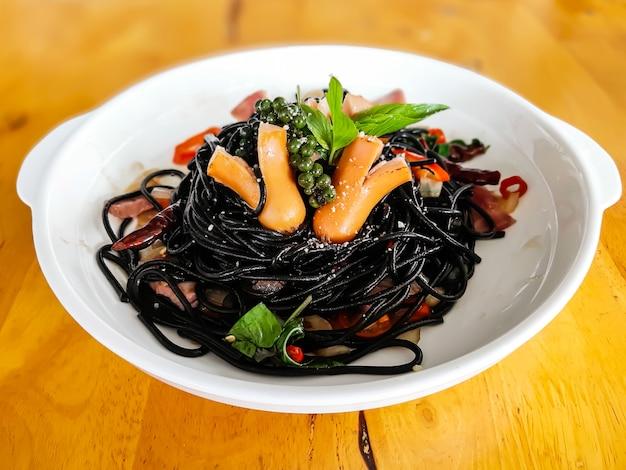 酔ったスパゲッティ鎖ソーセージ、唐辛子、バジルと白い皿に黒