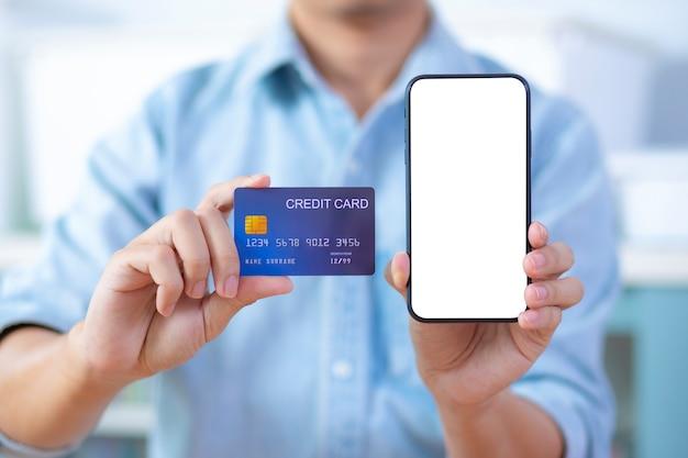 空白の画面のスマートフォンとクレジットカードを持っている男の手は、ライトブルーのシャツを着る