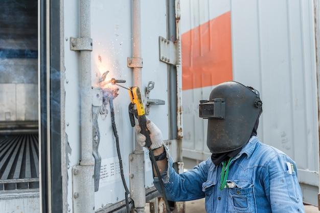 Рабочий сваривает стальную часть коробки контейнера