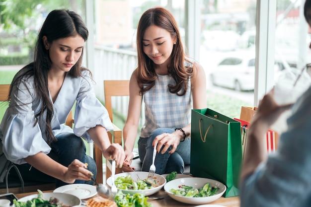Веселый друг улыбается и ест здоровую еду в ресторане
