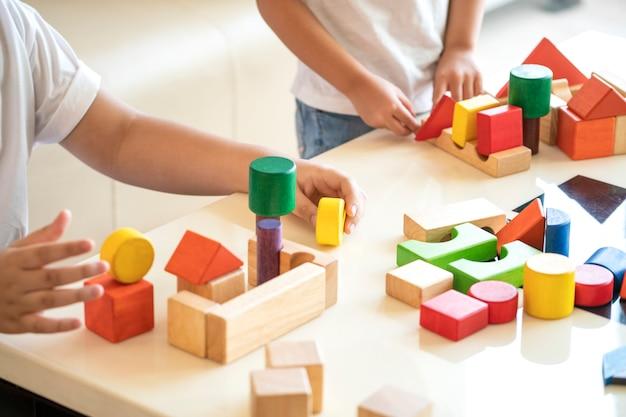 Дети играют в игрушки из деревянных блоков у себя дома