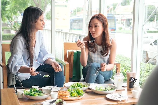 Веселый многорасовый друг улыбается и ест здоровую еду в ресторане