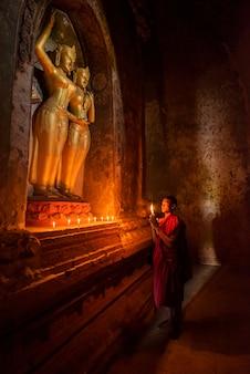 Новичок в мьянме молится статуе будды в старом городе баган, баган, мьянма