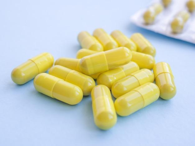 黄色い薬カプセル錠剤とブリスターパック。浅い被写界深度。医薬品抗生物質の錠剤。流行、鎮痛剤、ヘルスケア、治療薬、薬物乱用の概念。