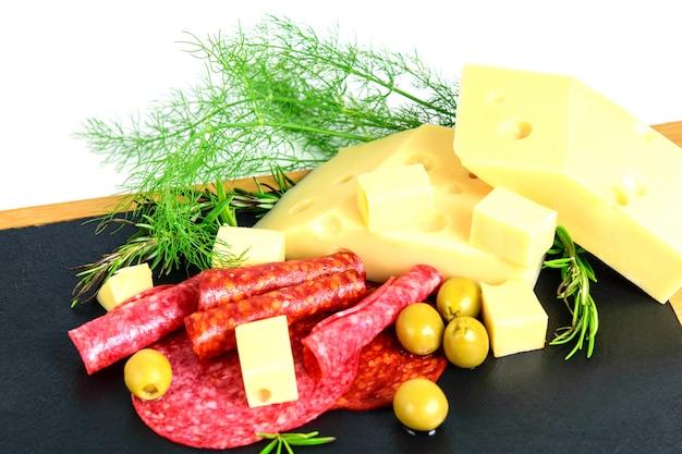 Ассорти из сосисок, сыра эмменталь, маслин и зелени на доске черных тапас.
