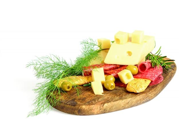 木製のまな板にスライスチーズ、チョリソ、サラミ、オリーブ、パン棒、ハーブ。