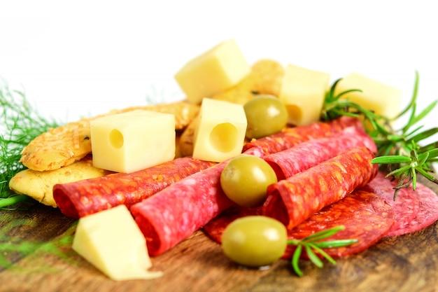 まな板のクローズアップ、スペースでチョリソ、サラミ、チーズ、オリーブ、パン棒、緑のハーブのスライス。