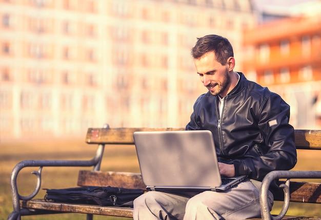若い男が彼のラップトップで座っています。