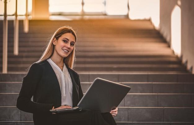 Деловая женщина сидит на лестнице с ноутбуком