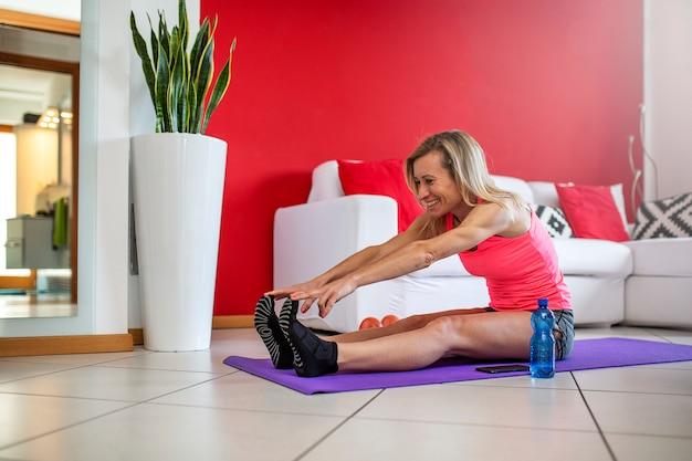 美しいブロンドの女性は、家のリビングルームで腹筋の演習を行います。